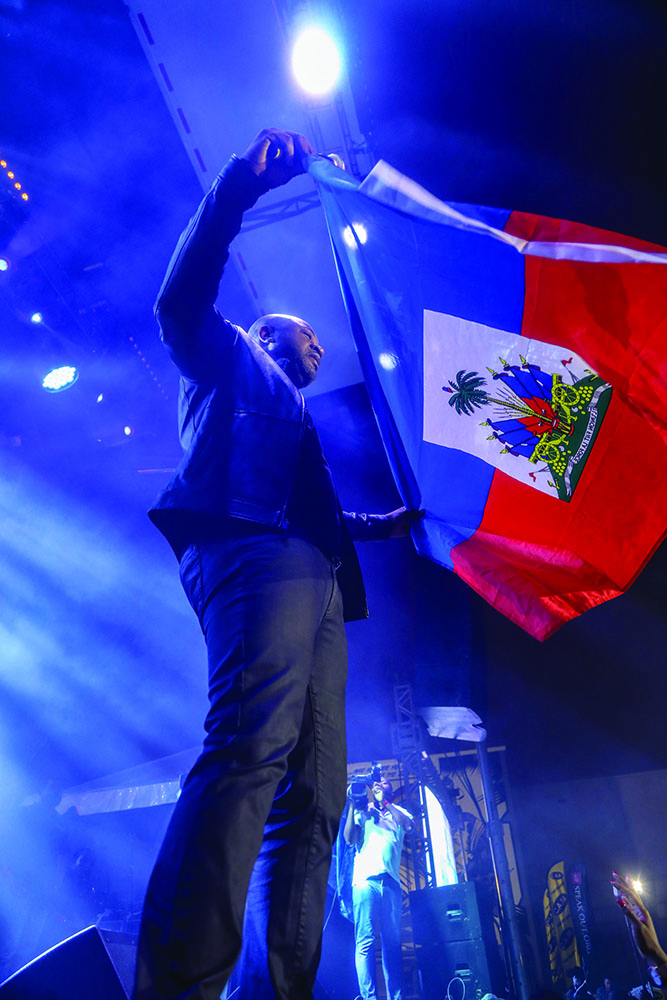 Arly Lariviere waving the Haitian Flag at the Haitian Compas Festival in Miami 2019